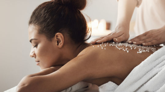 Young beautiful african girl resting enjoying spa health massage with sea salt.